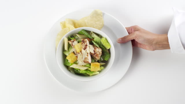 cu woman hand entering setting down round white plate with bowl of lettuce and pasta / omaha, nebraska, united states - human hand stock videos & royalty-free footage