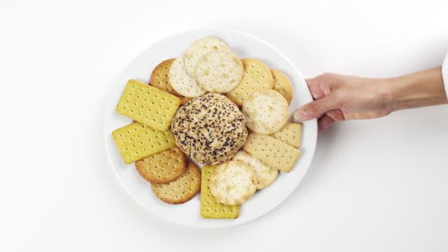 cu woman hand entering setting down round white plate with cheese ball and crackers / omaha, nebraska, united states - cheese ball stock videos and b-roll footage