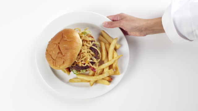 cu woman hand entering setting down round white plate with cheeseburger and french fries potatoes / omaha, nebraska, united states - cheeseburger stock videos & royalty-free footage