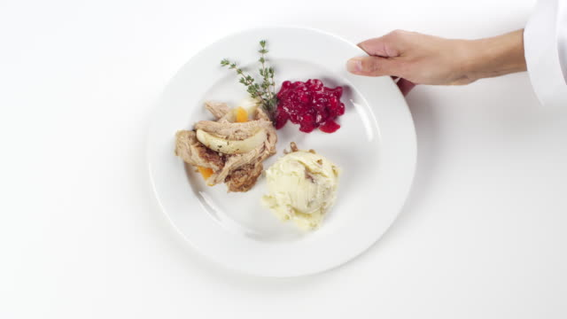 CU Woman hand entering setting down round white plate with chicken, mashed potatoes and cranberries / Omaha, Nebraska, United States