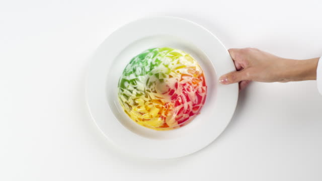 cu woman hand entering setting down round white plate with colorful red, yellow and green wiggly jello mold / omaha, nebraska, united states - gelatin stock videos and b-roll footage