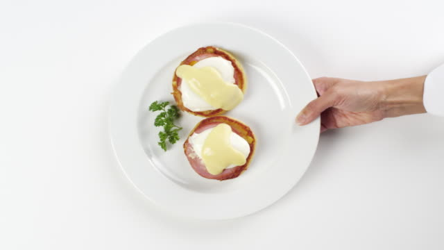 CU Woman hand entering setting down round white plate with eggs, benedict, hollandaise sauce, Canadian bacon, English muffin breakfast / Omaha, Nebraska, United States