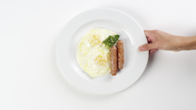 cu woman hand entering setting down round white plate with eggs over easy and two sausage links breakfast / omaha, nebraska, united states - human hand stock videos & royalty-free footage