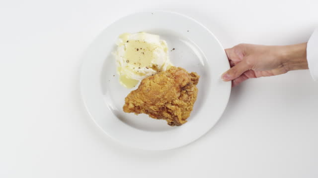 CU Woman hand entering setting down round white plate with fried chicken, mashed potatoes and gravy / Omaha, Nebraska, United States