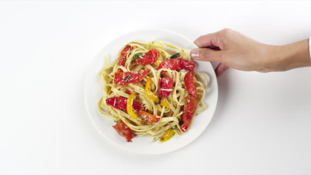 CU Woman hand entering setting down round white plate with pasta linguine, red pepper salad / Omaha, Nebraska, United States