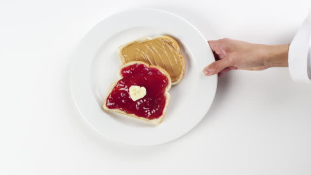cu woman hand entering setting down round white plate with peanut butter and strawberry jelly jam bread sandwich / omaha, nebraska, united states - preserve stock videos and b-roll footage