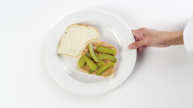 CU Woman hand entering setting down round white plate with peanut butter and pickles bread sandwich / Omaha, Nebraska, United States