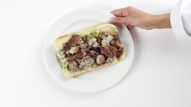 CU Woman hand entering setting down round white plate with philly cheese steak sandwich with green peppers / Omaha, Nebraska, United States