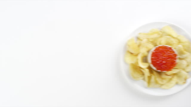 vídeos de stock, filmes e b-roll de cu woman hand entering setting down round white plate with potato chips and red caviar / omaha, nebraska, united states - snack salgado