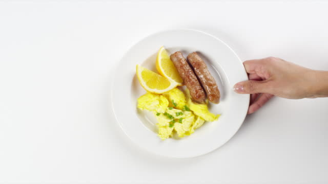 cu woman hand entering setting down round white plate with scrambled eggs and sausage breakfast / omaha, nebraska, united states - human hand stock videos & royalty-free footage