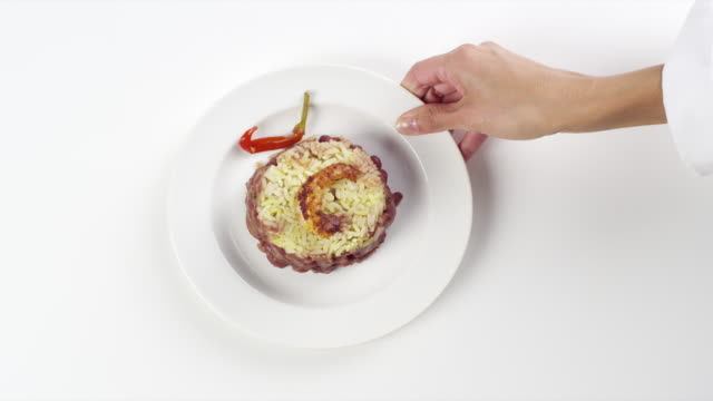CU Woman hand entering setting down round white plate with shrimp, white rice, beans and cajun hot pepper / Omaha, Nebraska, United States