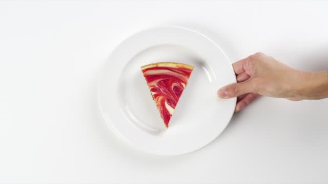 cu woman hand entering setting down round white plate with slice of cheesecake, with strawberry swirl dessert / omaha, nebraska, united states - ケーキ点の映像素材/bロール