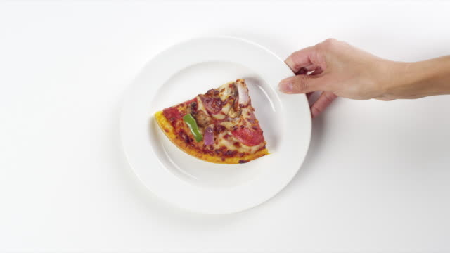 vidéos et rushes de cu woman hand entering setting down round white plate with slice of cheese, pepperoni, mushroom, onion and green pepper / omaha, nebraska, united states - part of