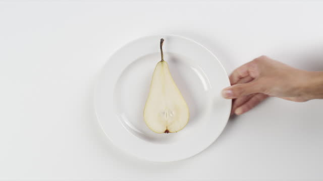 cu woman hand entering setting down round white plate with sliced pear / omaha, nebraska, united states - pear stock videos & royalty-free footage