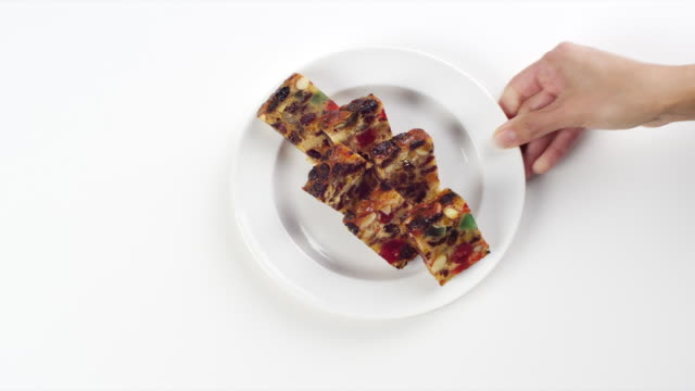 CU Woman hand entering setting down round white plate with slices of holiday, Christmas fruit cake / Omaha, Nebraska, United States