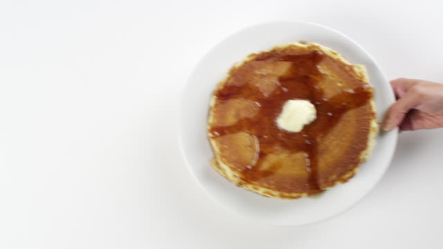 cu woman hand entering setting down round white plate with stack of breakfast pancakes, syrup and butter / omaha, nebraska, united states - comfort food stock videos & royalty-free footage