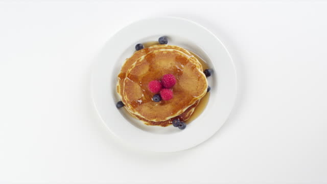 cu woman hand entering setting down round white plate with stack of pancakes, syrup, blueberries, raspberries dessert / omaha, nebraska, united states - pancake stock videos & royalty-free footage