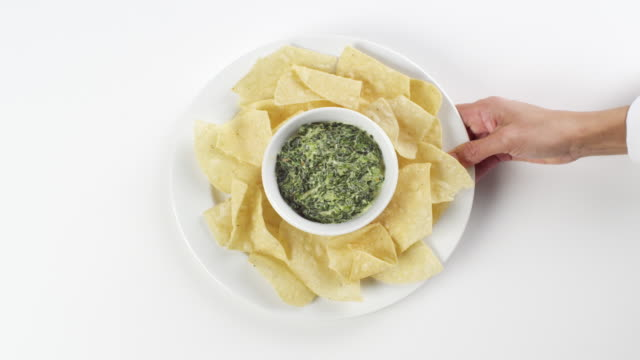 cu woman hand entering setting down round white plate with taco chips and artichoke dip / omaha, nebraska, united states - dipping stock videos & royalty-free footage