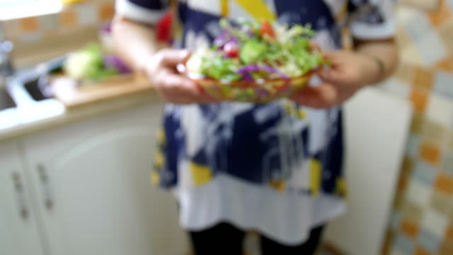 Woman hand holding a bowl of salad