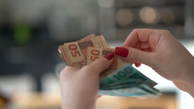 woman hand holding a the currency of reais, brazilian money - exchange rate stock videos & royalty-free footage