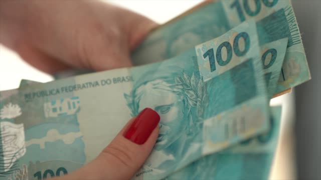 woman hand holding a the currency of reais, brazilian money - brasilia stock videos and b-roll footage