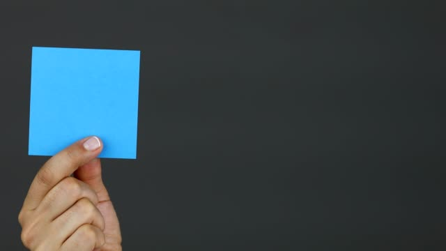 vidéos et rushes de note bleue de bâton de fixation de main de femme - panneau d'information