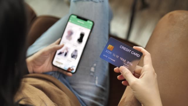 woman hand holding credit card on her hand online shopping on her smart phone - acquisto con carta di credito video stock e b–roll
