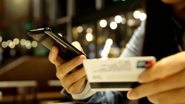vidéos et rushes de main de femme tenant le téléphone mobile et carte de crédit en ligne shopping - endettement