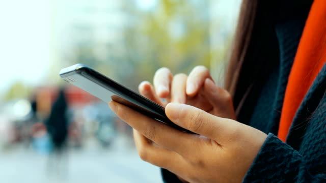 Main de femme tenant le téléphone portable marche sur la rue