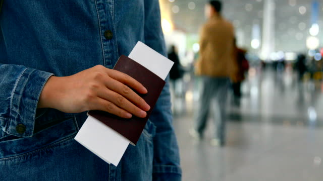 Woman hand holding passport in airport