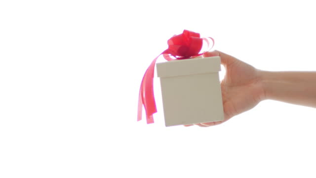 Woman hand Holding White gift box with red ribbon on white background