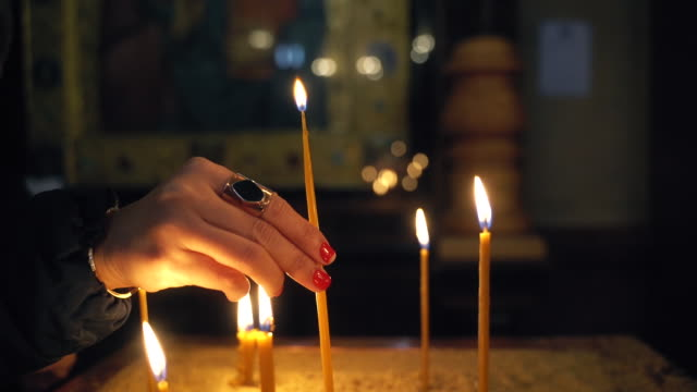 woman hand lighting up a candle in church - candlelight stock videos & royalty-free footage