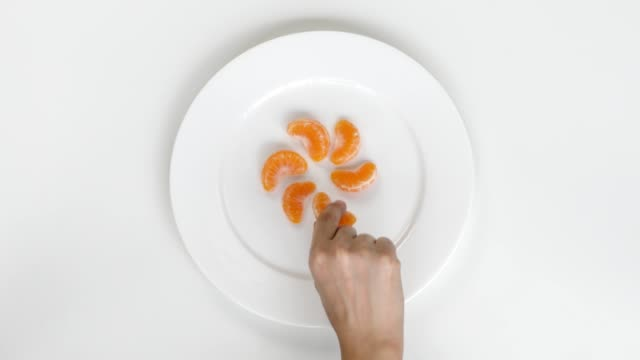 woman hand picking one tangerine piece from plate - ascorbic acid stock videos & royalty-free footage