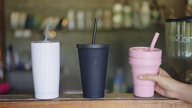 woman hand placing silicone traveling mug onto bar counter - reusable stock videos & royalty-free footage
