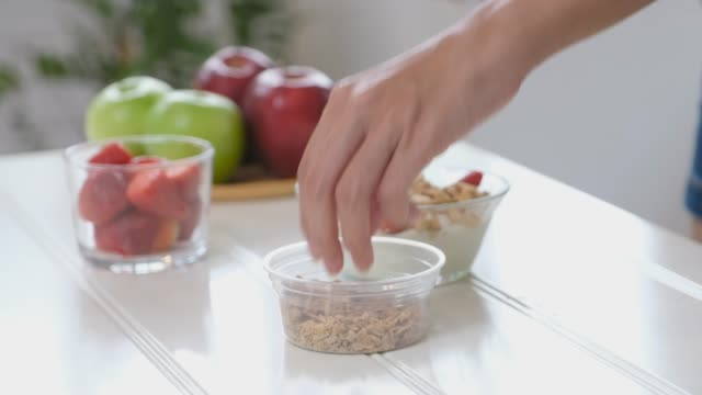 朝の食事のための健康食品を準備する女性の手, yoguart と果物との, 健康的なライフスタイルの概念 - アーモンド点の映像素材/bロール