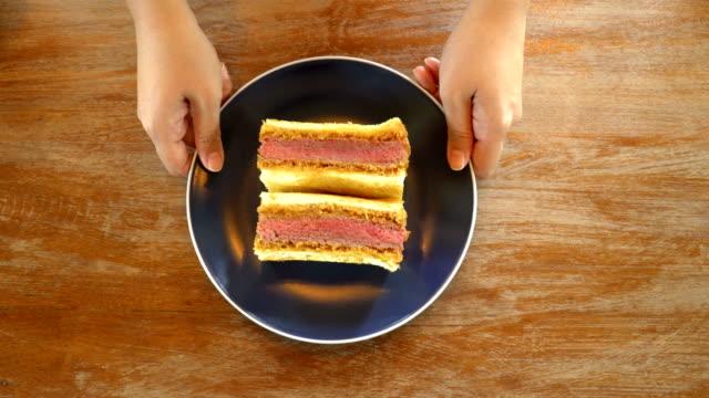 ビーフカツサンドイッチをプレゼントする女性ハンド - 食べ物 サンドイッチ点の映像素材/bロール