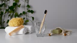 Woman hand puts bamboo toothbrush in glass among eco-friendly bathroom accessories: natural sea sponge, soap in organic saver bag, wooden comb. Zero waste spa and bath products. Natural skin care
