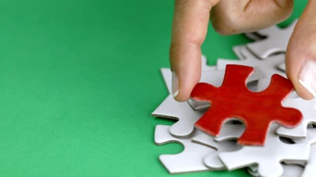 una mano donna mettendo in un puzzle rosso piastrella su una pila di bianco - puzzle video stock e b–roll