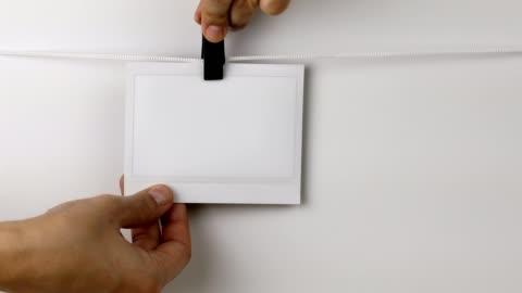 vídeos y material grabado en eventos de stock de mujer quitando el marco instantáneo de la foto colgando de una cuerda - transferencia de impresión instantánea