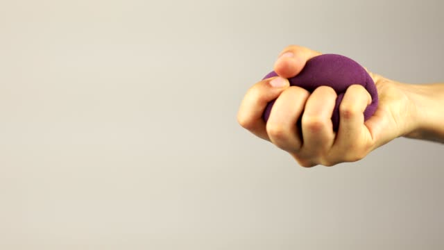 a woman hand repeatedly squeezes and releases a purple stress ball - physical pressure stock videos & royalty-free footage
