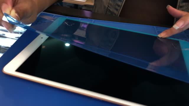 stockvideo's en b-roll-footage met de handbeschermende film van de vrouwscherm voor digitale tablet - poreus