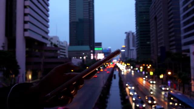 vídeos de stock, filmes e b-roll de mão de mulher enviar messege com bokeh da luz - send
