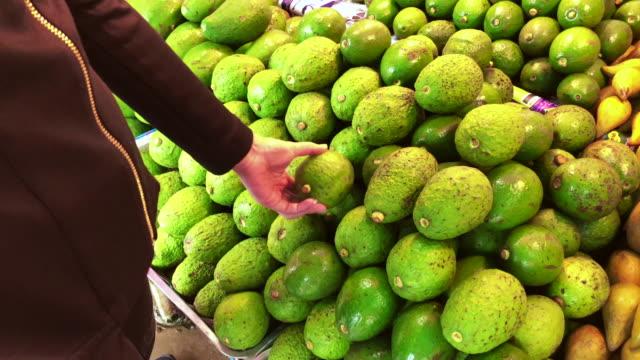 vídeos y material grabado en eventos de stock de mano de mujer compra aguacate en supermercado, tailandia - aguacate