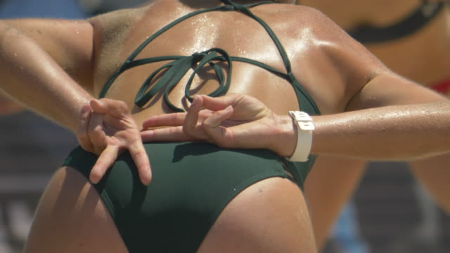 stockvideo's en b-roll-footage met woman hand signaling to her partner playing beach volleyball. - slow motion - getal 2