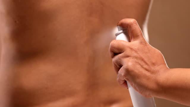 cu woman hand spraying relief spray on her husband painful lower back / new delhi, delhi, india - dorso umano video stock e b–roll