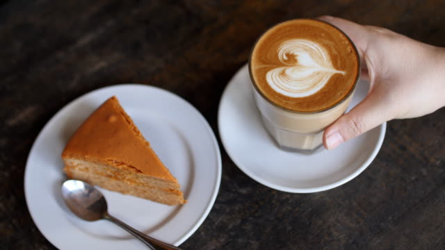 woman hand take a coffee with cake in coffee cafe , slow motion - frothy drink stock videos & royalty-free footage