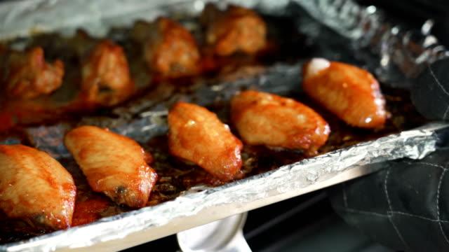 stockvideo's en b-roll-footage met 4k rt vrouw de hand nemen gebakken kip uit de oven. - dierenvleugel