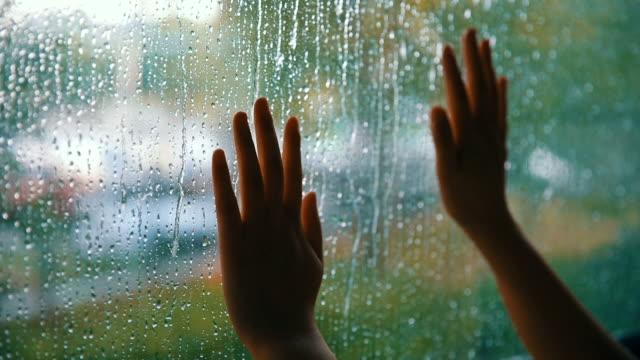vídeos y material grabado en eventos de stock de ventana de toque de mano de mujer con gotas de lluvia - mirar por la ventana
