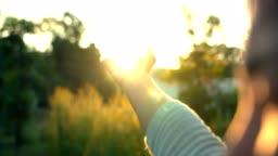 Woman hand touching sun light