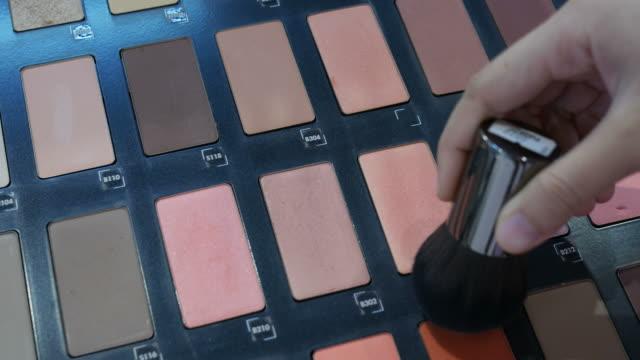 vídeos de stock, filmes e b-roll de mão de mulher, usando o pincel blush maquiagem paleta - blush